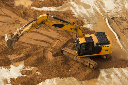 View from above at Working Excavator Tractor Digging A Trench.