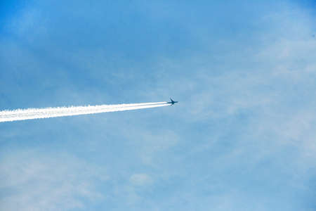 airplane contrail against clear blue sky. sunny day