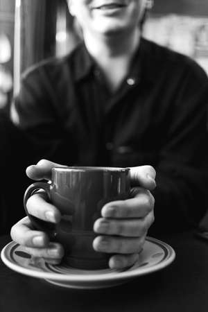 Cropped view at a young man holding coffe cup both hands in a coffe shop. Stock Photo