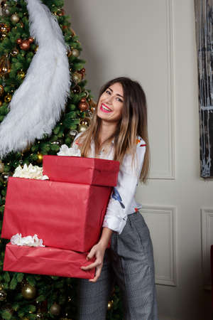 christmas, x-mas, winter, happiness concept - smiling woman fashion style wear clothes casual white suit shirt and pants with gift boxes.