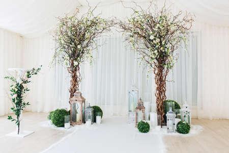 Innenhochzeitszeremonie mit weißem Hochzeitsbogen, verziert mit Blumen und großen weißen Kerzen.