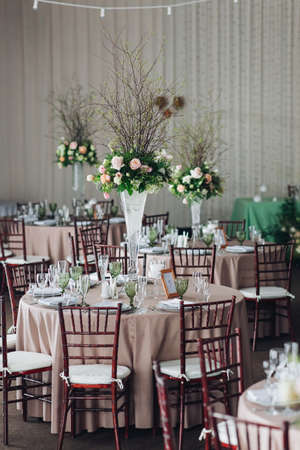 Bellissima composizione con fiori sui tavoli e candele per gli invitati ad un matrimonio o ad una festa di compleanno.