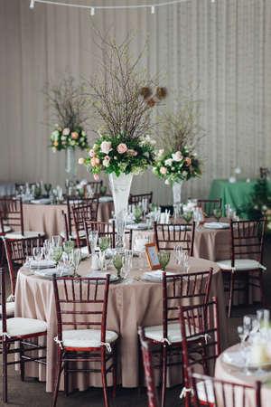 Piękna kompozycja z kwiatami na stołach i świecami dla gości na weselu lub przyjęciu urodzinowym.
