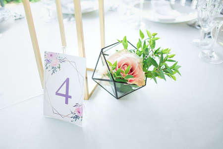 Beautiful composition with flowers on the tables and candles for guests at a wedding or a birthday party.