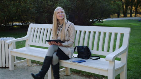 Young Beautiful Woman Sits On The Bench In Autumn Park And Works On The Tablet. Stockfoto