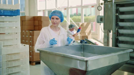 Candy factory. Factory worker checking packing machine. Young woman in uniform inspecting packing machine while working in confectionery factory. Stockfoto