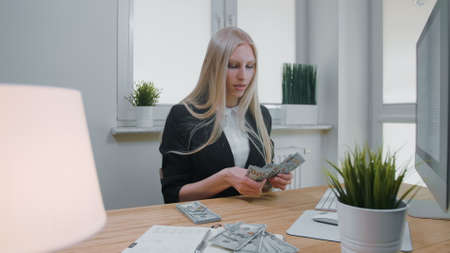 Beautiful young blond woman in business suit, sitting in office at light wooden desk with computer concentrating on counting large pile of cash in hands