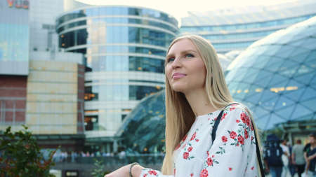 Amazed woman in modern city. Young lady in elegant outfit admiring view in astonishment while standing on background of futuristic building on street of modern city.