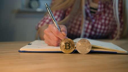 Crop view of female hands in checkered shirt holding shiny metal pen, and writing into daily planner with bitcoins placed on edges on foreground at night.