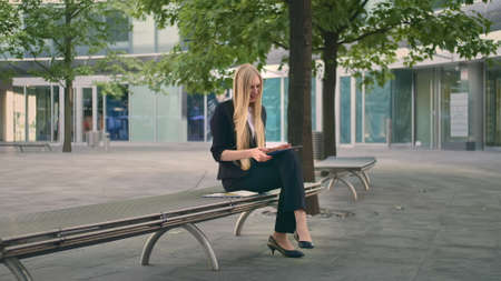 Formal business woman sitting on bench in office patio and browsing tablet in leisure. Stockfoto