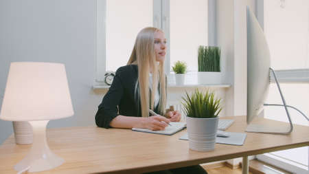 Attractive young blond female in elegant jacket sitting with pen and notebook at desk with computer and looking excitedly at monitor screen Stockfoto