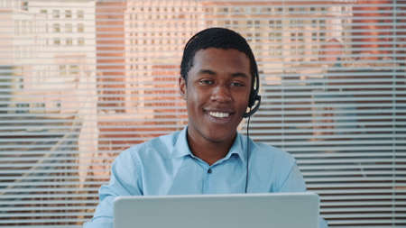 Black man in headset speaking with somebody and working on the computer. He working in modern international customer support office. There are skyscrapers in the background.
