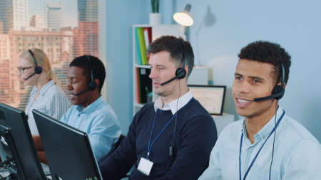 Cheerful customer support agent of mixed ethnicity talking on phone with a headset. He working in modern call center office.