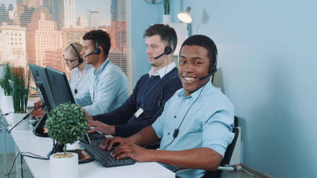 Medium long shot of Black customer support agent working in busy call center by talking to the international client. His multiethnic team also taking calls. Stockfoto