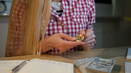 Crop view of blond female in checkered casual shirt, sitting at wooden table with dollar cash on it turning bitcoin over in hands studying it Stockfoto