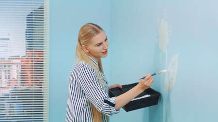 Woman painting flowers on the blue wall in a modern office.