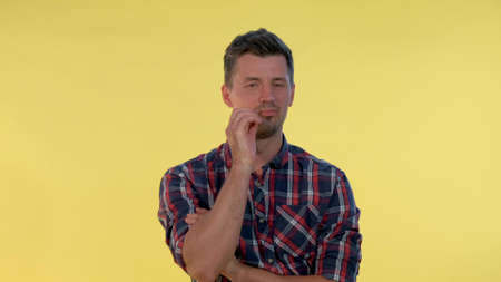 Close-up of handsome man promising to keep silence. He zipping his lips. Yellow background.