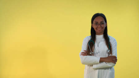 Black female doctor in lab coat smiling to the camera on yellow background. She is with stethoscope on shoulders. Stockfoto