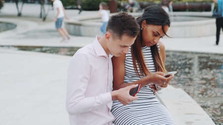 Black girlfriend with boyfriend on date not talking, but chatting with somebody by smartphones. They probably have problem with communication.