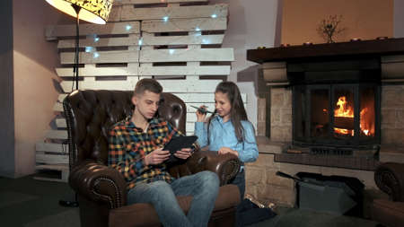 Small girl disturbing her brother to use the tablet. They spending time in a cozy living room with big fireplace