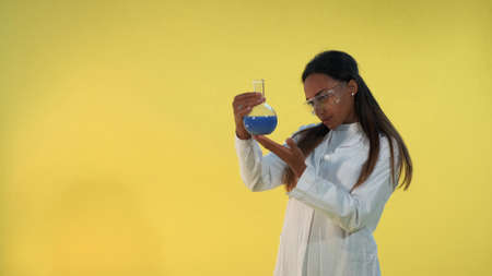Black female scientist in lab coat looking on flask with experimental liquid on yellow background. She also has safety glasses on eyes. Stockfoto