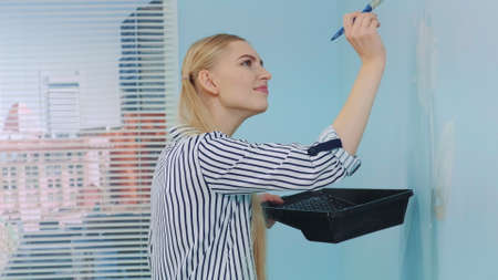 Close-up shot of woman drawing a flower on a blue wall in a house room. In the background there are skyscrapers at day. Stockfoto
