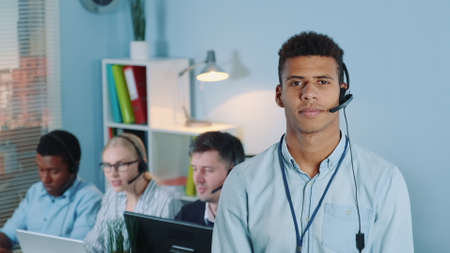 Portrait of multiracial customer service operator in headset smiling to the camera. Working colleagues are in the background. Stockfoto