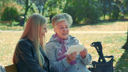 Medium shot of old woman showing her pretty granddaughter a letter. They sitting on a bench in beautiful park one autumn day. Stockfoto