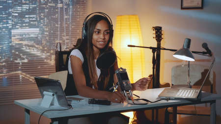 Multiracial female journalist doing online interview on the computer in home recording studio in the evening. Woman is in headphone.
