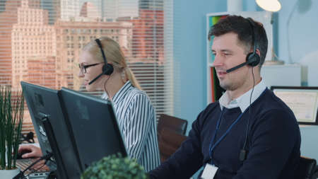 Handsome man service operator talking to the client on phone in call center. He using headset helping people.