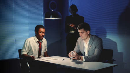 Accused young man crumpling a document with accusation in interrogation room after black detective gave him to sign it.