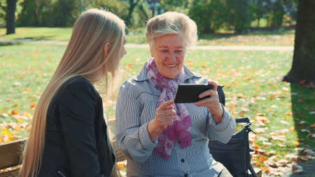 Beautiful blonde girl with elder woman sitting on bench and looking something on smartphone. They spending time in a big autumn park with golden leaves on a grass.