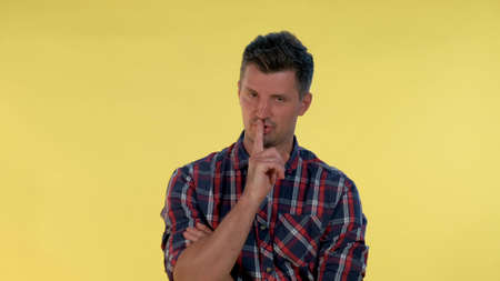 Close up of young man making a hush gesture on yellow background. It must be quite there. Stockfoto