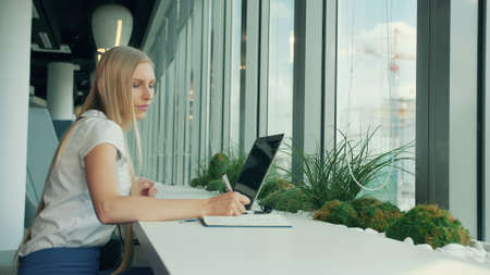 Side view of businesswoman writing on paper while sitting with laptop at table near window in modern office