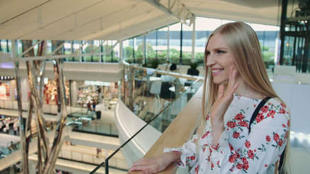 Cheerful woman greeting acquaintance in mall. Side view of lovely young female smiling and waving hand while greeting acquaintance in huge modern mall.