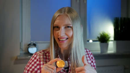 Cheerful young blond woman in casual clothes, sitting at dark window at night holding bitcoin and doing thumbs up gesture smiling and looking at camera Stockfoto