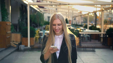 Elegant blond woman in suit walking on street and browsing smartphone with smile against urban background.