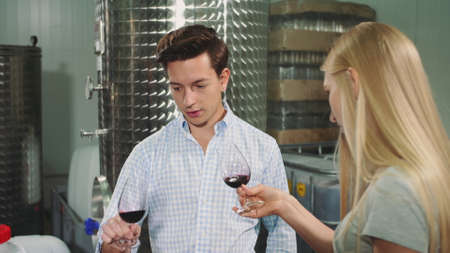 People degustation wine with sommelier. Sommelier showing how to taste wine correctly to young visitors of viticulture production.