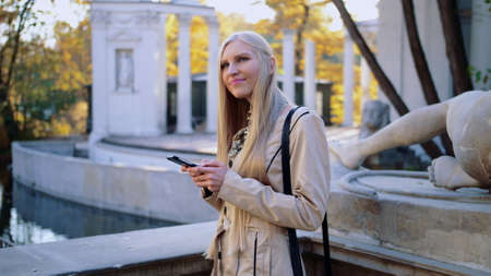 Cheerful blonde woman in beige coat in autumn park, looking at her smartphone and typing a reply on social media site. Looks at the camera. Tracking slow motion medium shot