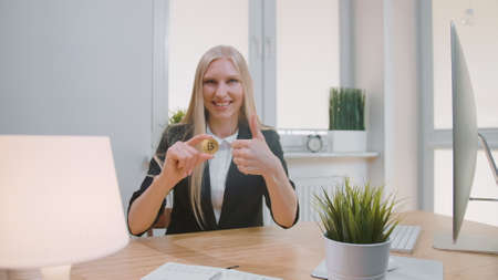 Smiling cheerful blond woman in office suit, sitting at workplace with computer and showing bitcoin in hand doing thumbs up gesture and looking at camera