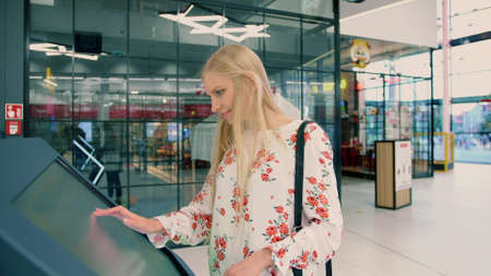 Woman near navigation board in mall. Side view of lovely young female in casual outfit looking for right direction on navigation board in modern mall. Stockfoto