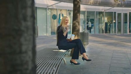 Elegant modern woman sitting on bench and waving with hand to friend while speaking on smartphone outdoors