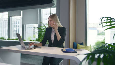 Stylish young blond woman working in office at table surfing laptop and having phone call while smiling Stockfoto