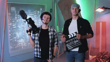 Camera man and producer assistant smiling to the camera and showing their equipment: movie camera and movie clapper board.