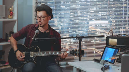 Talented guitarist in hat and trendy casual clothes playing guitar and singing in home recording studio. There are skyscrapers in the background. Stock Photo