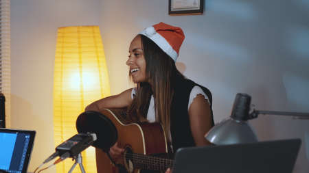 Beautiful black woman in Santa hat singing and playing guitar on Christmas Eve in cozy home studio. In front there is a recording equipment. Stock Photo