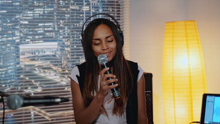 Close-up of beautiful multiracial girl in headphone singing into microphone and recording a song in home studio with skyscrapers in the background.