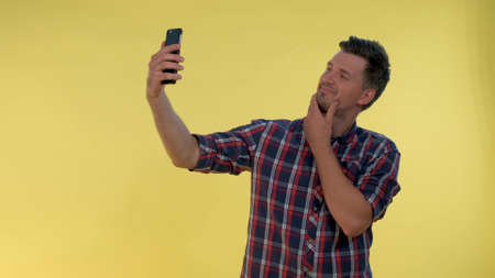 Attractive tall boy making selfie on smartphone. He smiling and standing against yellow background.