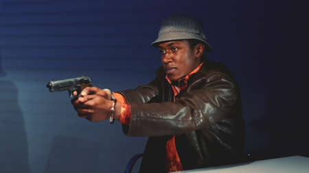 Close-up of black criminal grabbing the gun and threatening to harm cops. He trying to escape from interrogation room.