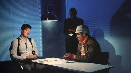 Medium shot of Police detective giving black murder criminal a document to sign a confession about the crime, but he refusing it, throwing away a piece of paper.